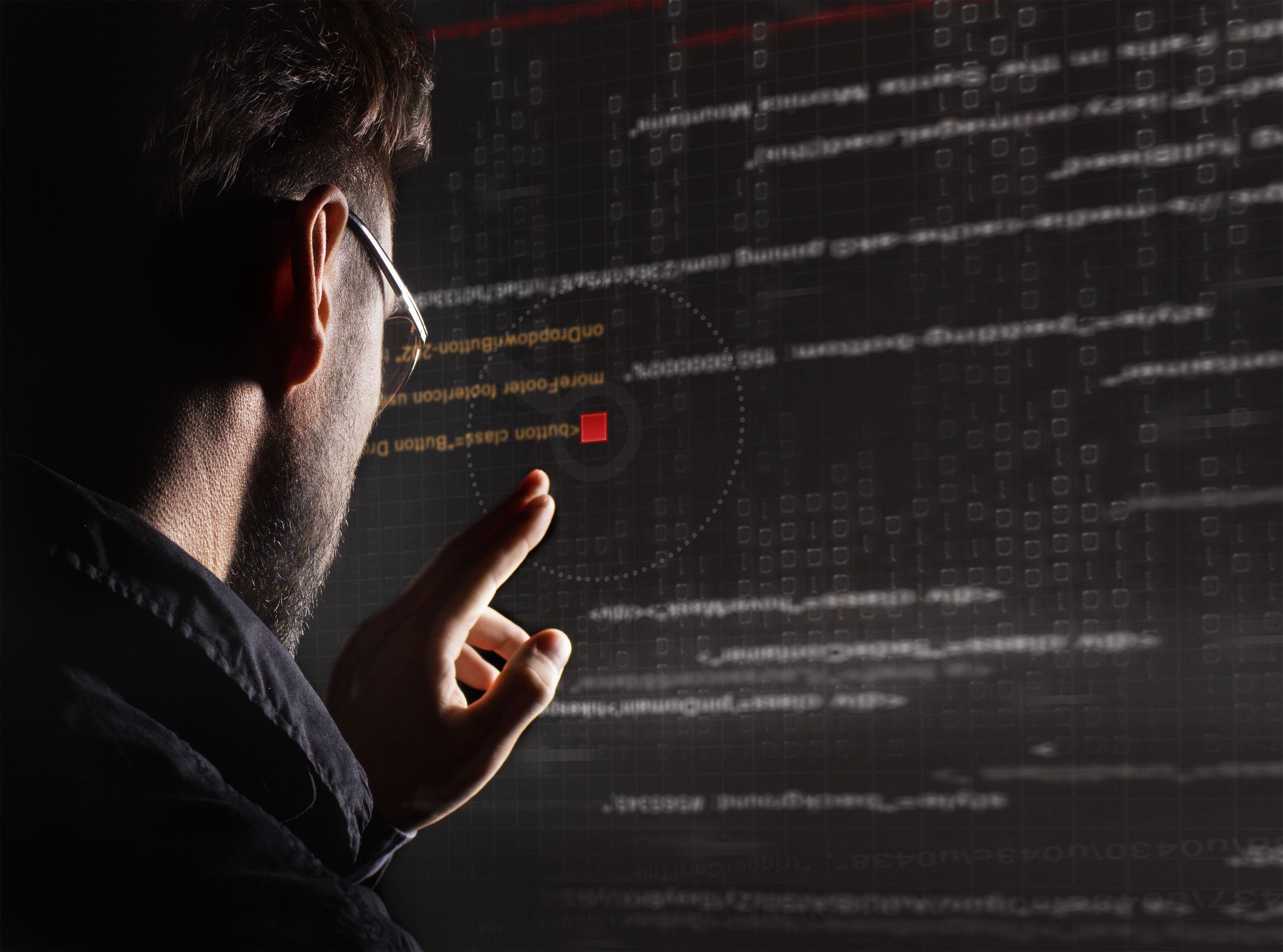 Hacker barbat care se uita pe un monitor