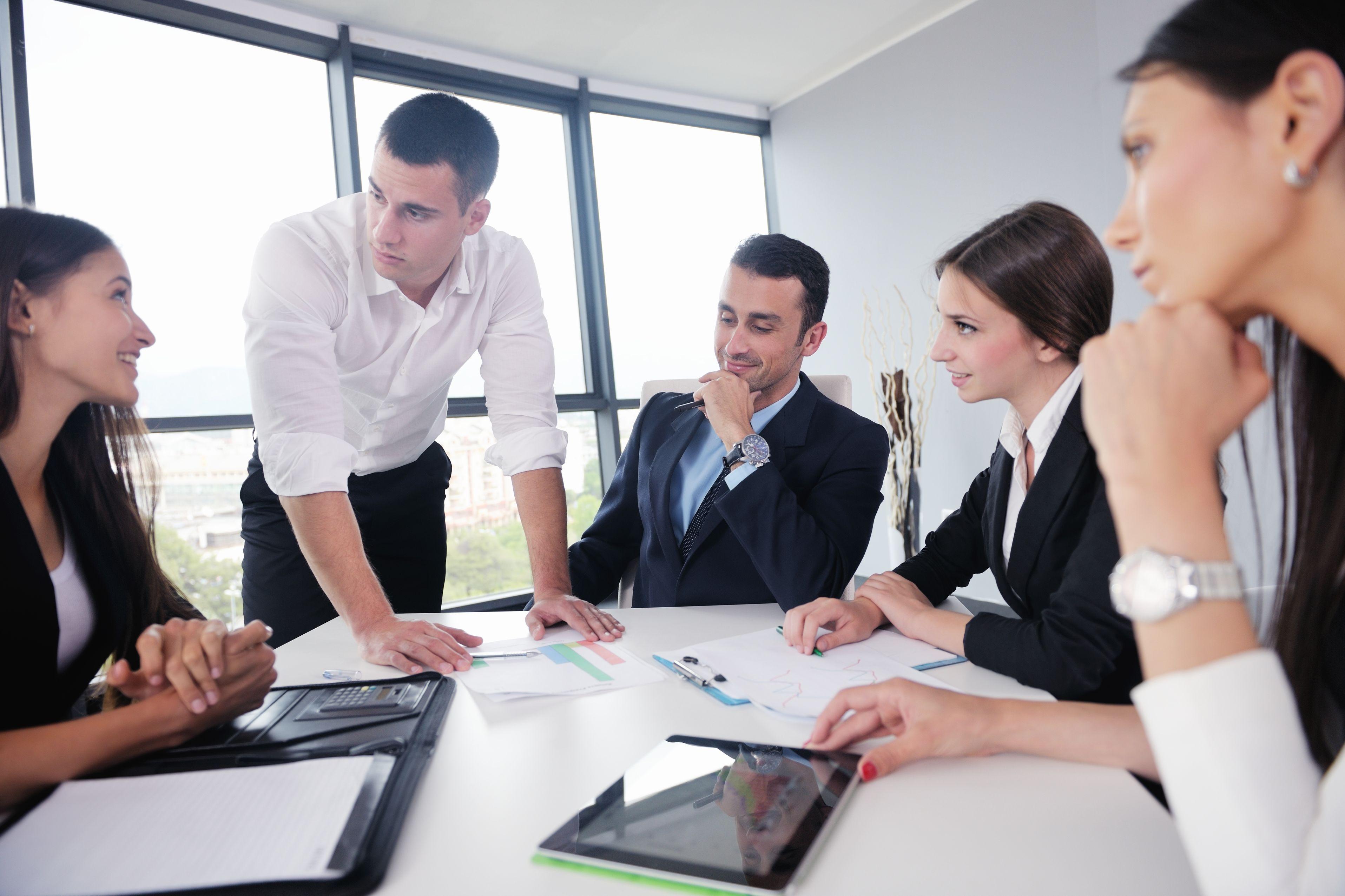 Mai mulți colegi de serviciu stau la o masă și discută.