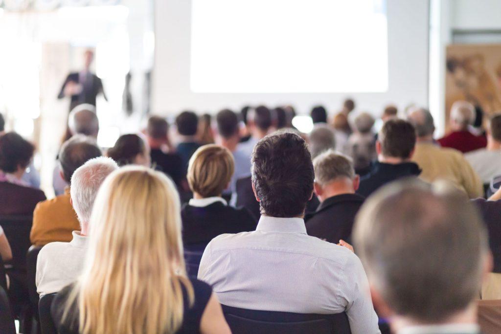 Multi oameni intr-o sala de training care urmaresc prezentarea unui speaker