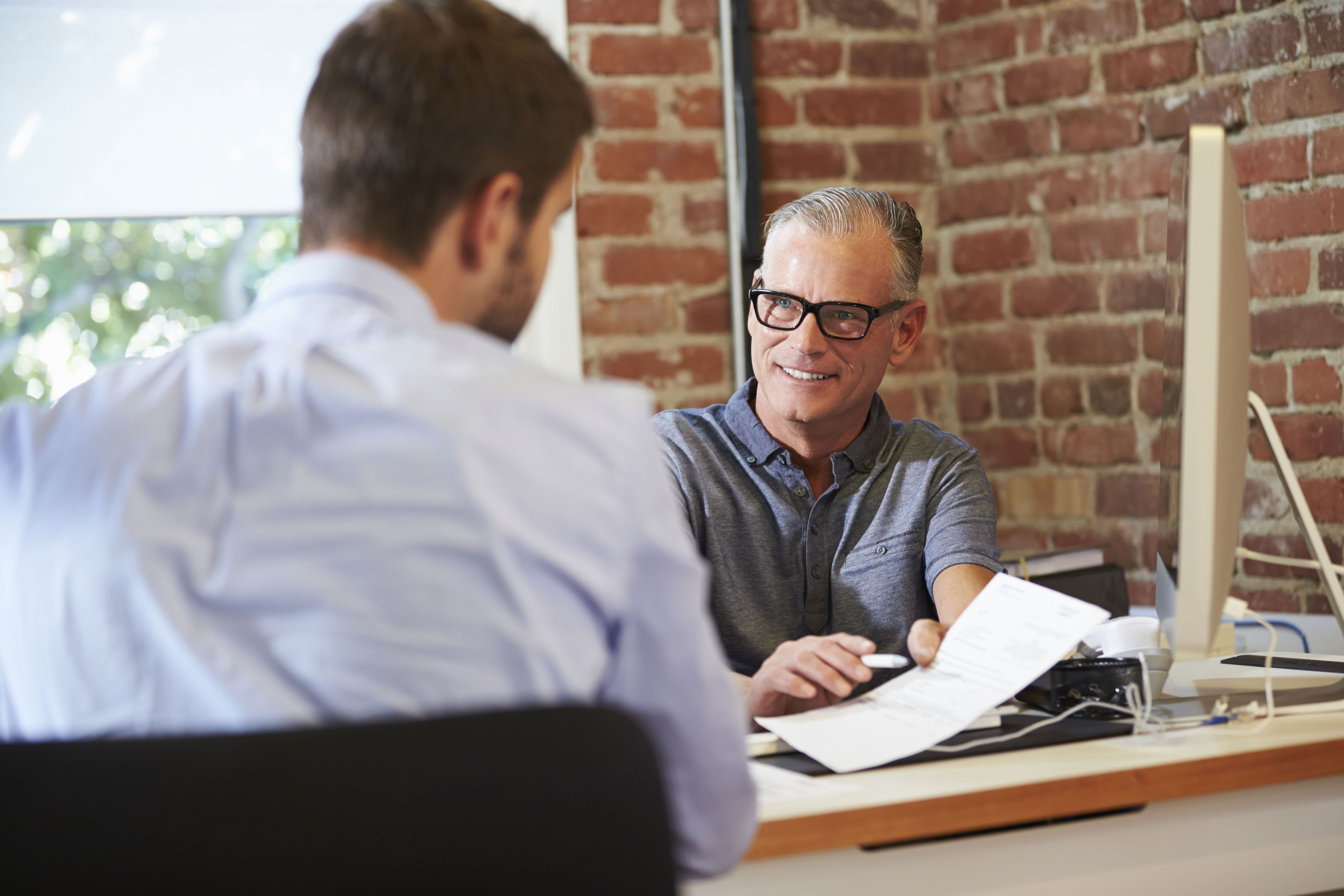 Discuție între un recrutor bărbat și un candidat bărbat.