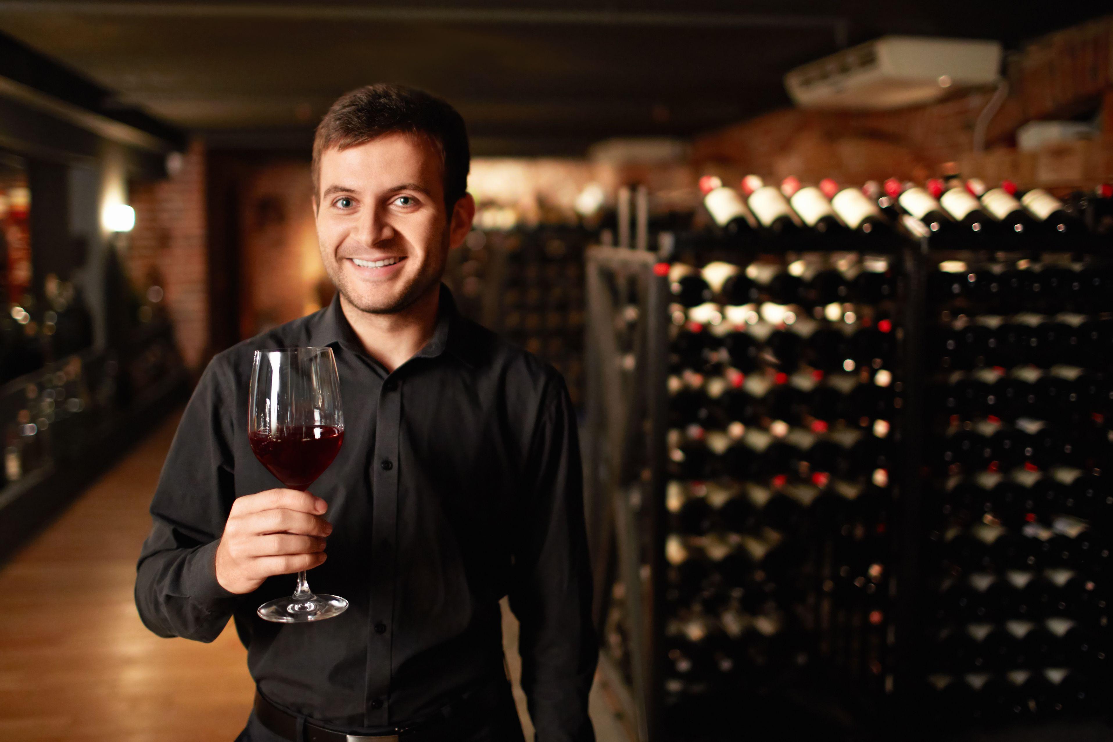 Bărbat cu un pahar de vin în mână, aflat într-o pivniță