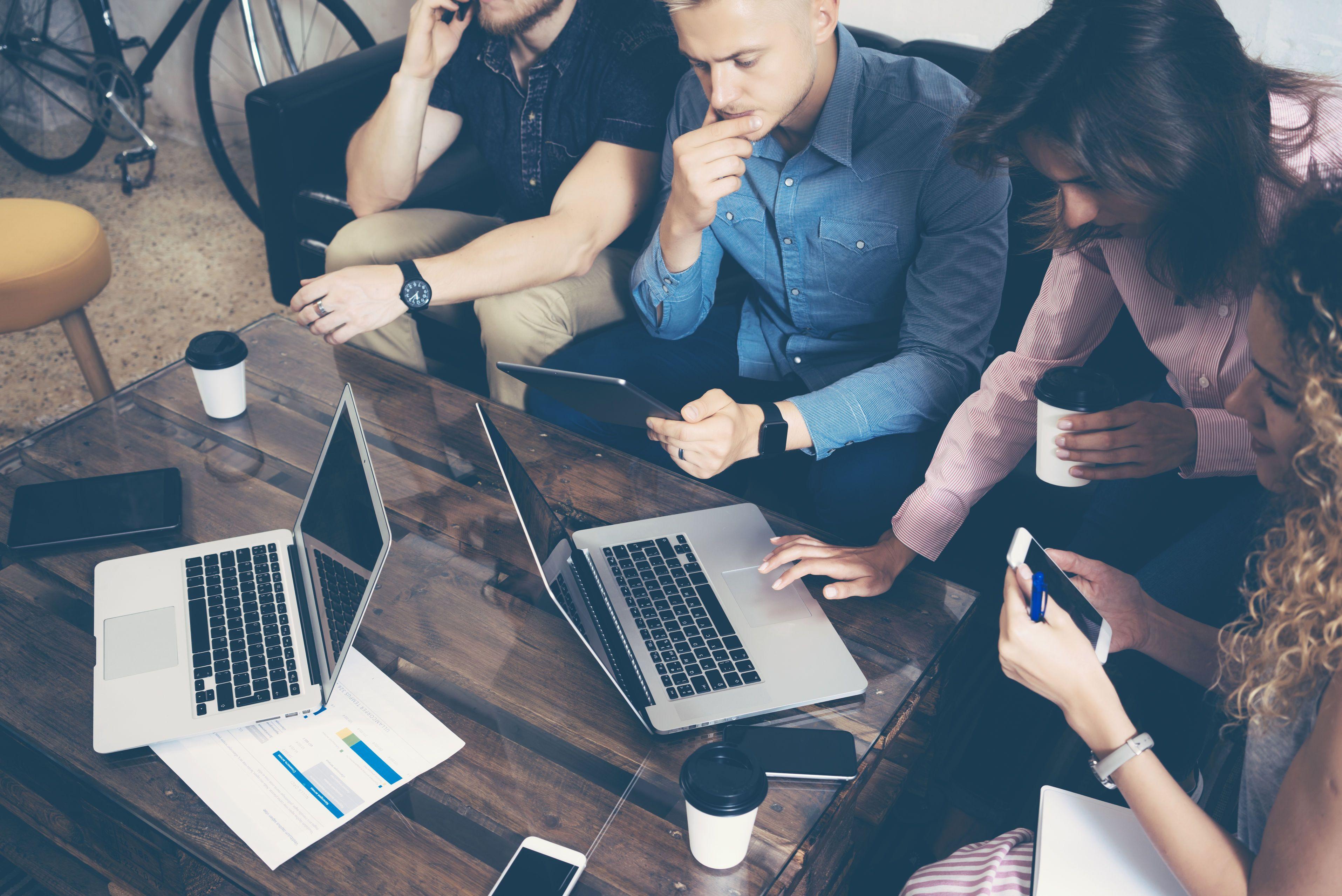 Spațiu de lucru la comun. Mai mulți tineri care lucrează pe laptopuri și tablete la un proiect comun.